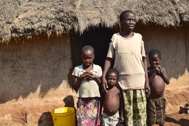 A widowed grandmother raising 3 kids in this thatch-roof hut